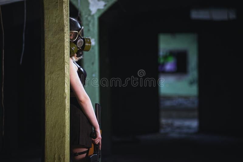 Beitragsapocalypse-Mädchenstand des schönen, jungen Mädchens in verlassener Fabrik mit Gasmaske und Maschinengewehr stockbild