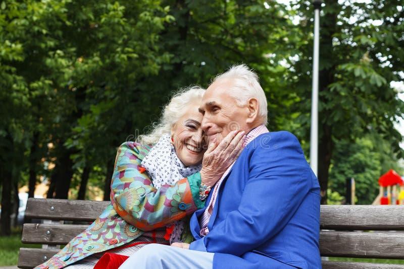 Bejaard familiepaar die op een bank in een stadspark spreken Het gelukkige oudsten dateren royalty-vrije stock foto's