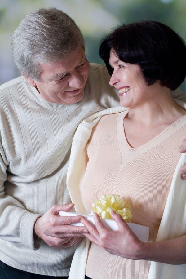 Bejaard gelukkig paar met giftbox, het glimlachen en het omhelzen royalty-vrije stock foto's