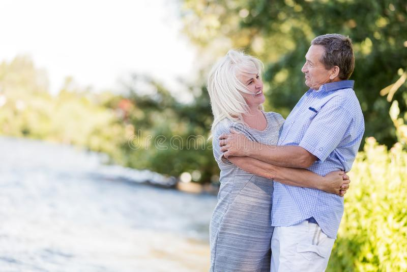 Bejaard huwelijk die door het meer koesteren stock foto's