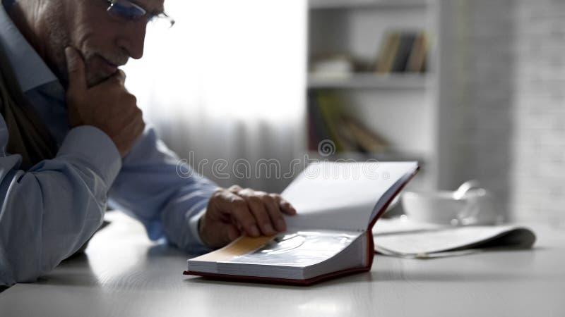 Bejaard mannetje die foto's in album bij keukenlijst bekijken, prettig geheugen stock foto