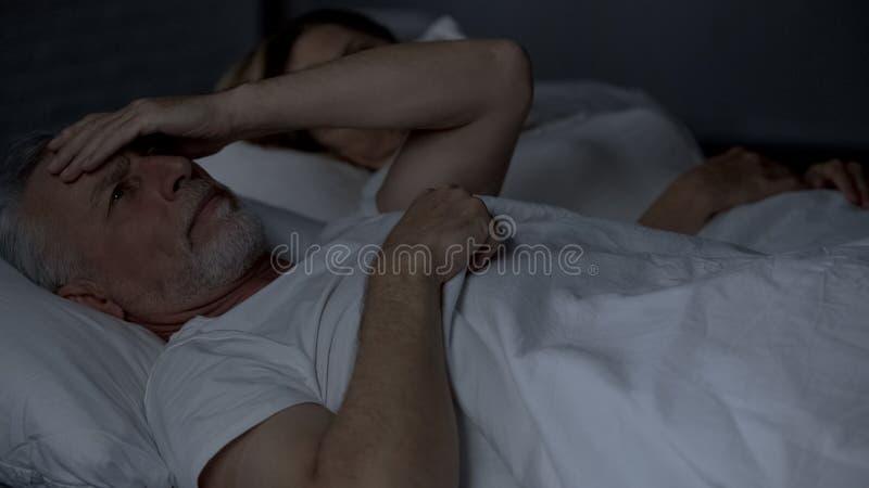 Bejaard mannetje die slapeloos in bed liggen die aan hoofdpijn lijden, die hoofd, problemen wrijven stock fotografie
