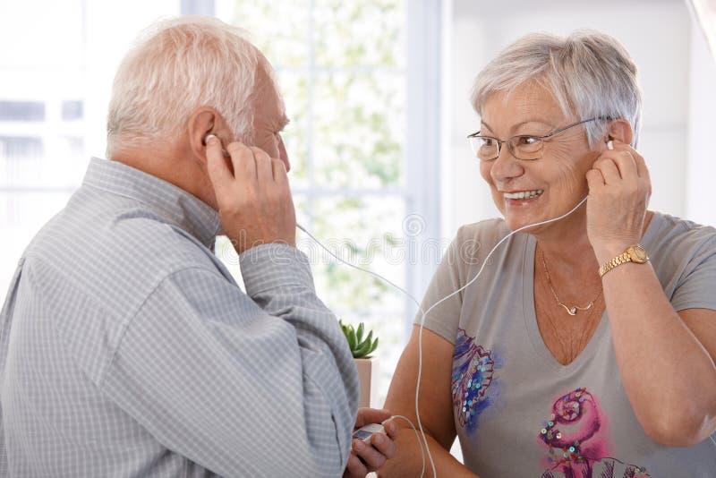 Bejaard paar dat aan muziek op mp3 speler luistert stock afbeeldingen