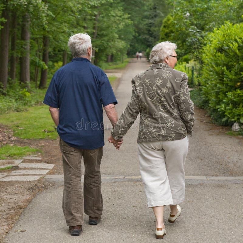 Bejaard paar dat hand in hand loopt royalty-vrije stock fotografie