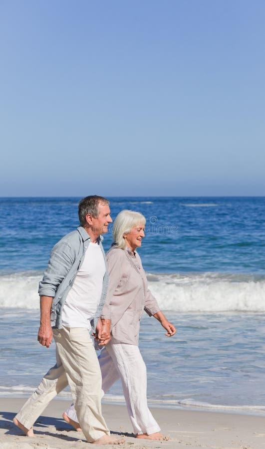 Bejaard paar dat op het strand loopt royalty-vrije stock afbeeldingen