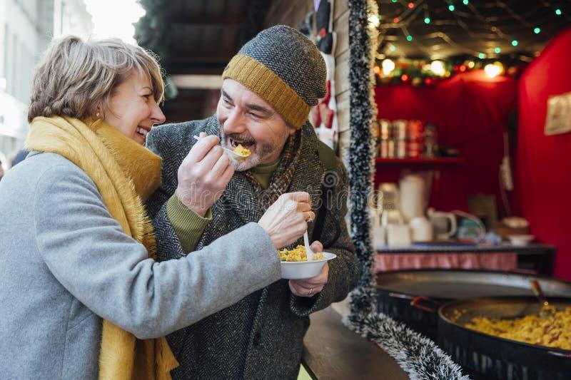 Bejaard Paar die bij Kerstmismarkt eten stock foto