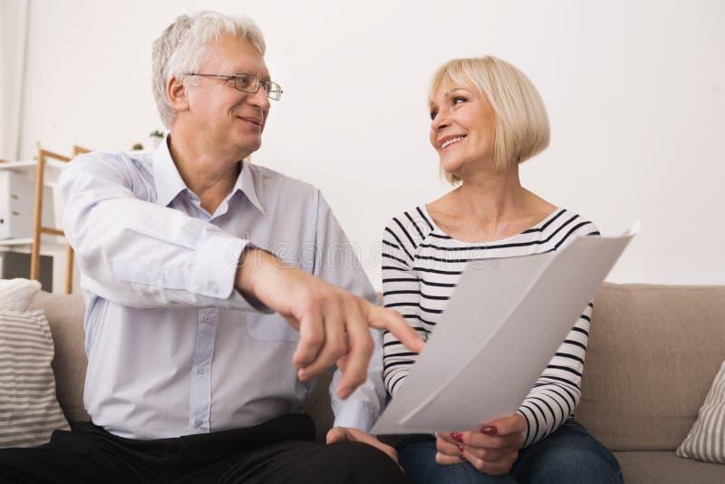 Bejaard paar die documenten bespreken, die elkaar bekijken stock foto's