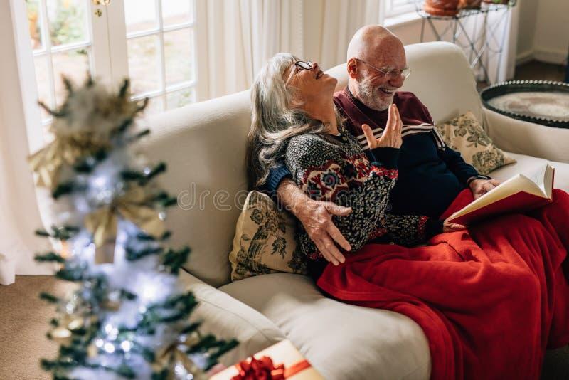 Bejaard paar die een boekzitting op bank thuis lezen stock fotografie