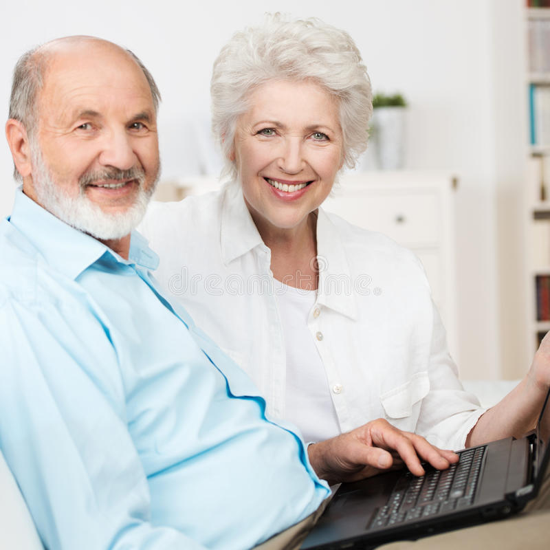 Bejaard paar die een laptop computer met behulp van royalty-vrije stock foto