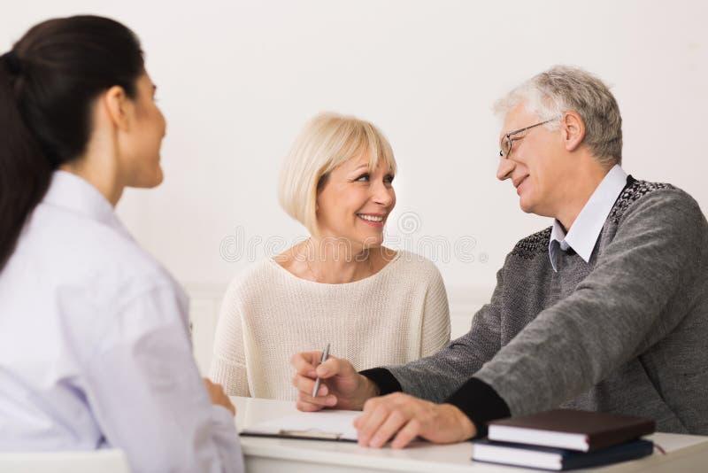 Bejaard Paar die Medische Ziektekostenverzekering kopen en Makelaar raadplegen stock foto