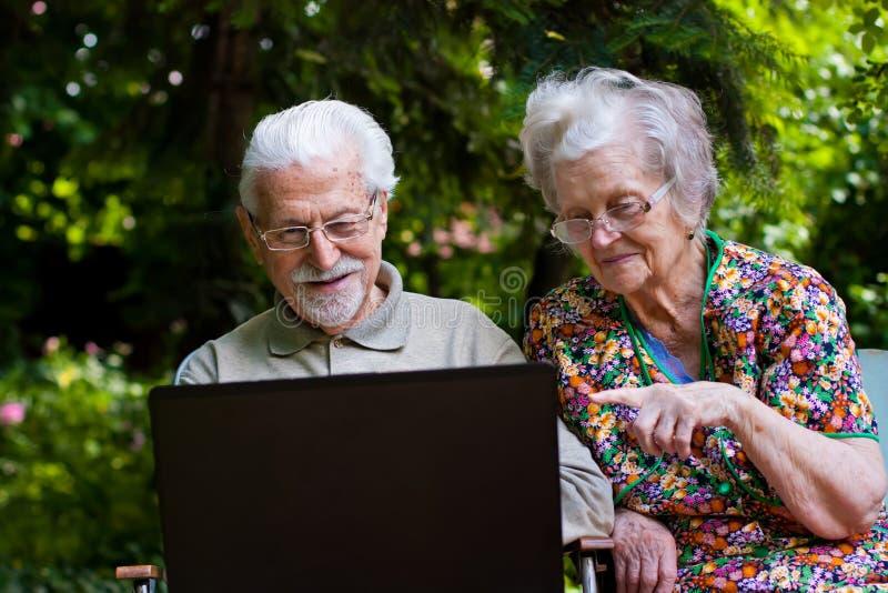 Bejaard paar die pret met laptop hebben in openlucht royalty-vrije stock foto's