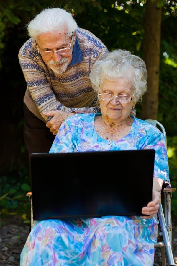 Bejaard paar die pret met laptop hebben in openlucht stock foto's