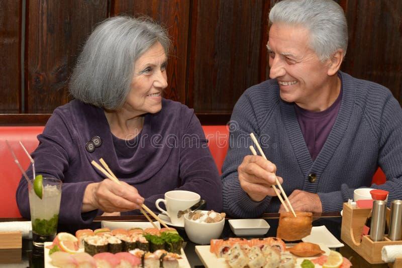 Bejaard paar die sushi eten royalty-vrije stock afbeeldingen