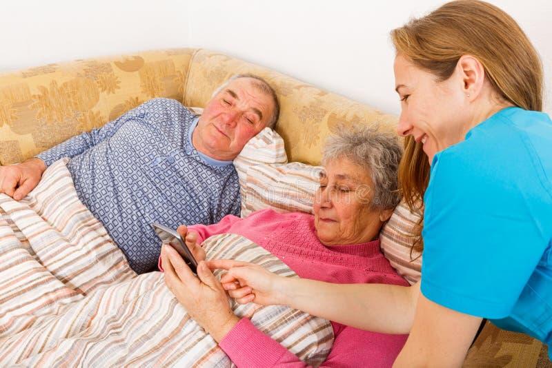 Bejaard paar en jonge verzorger stock foto's