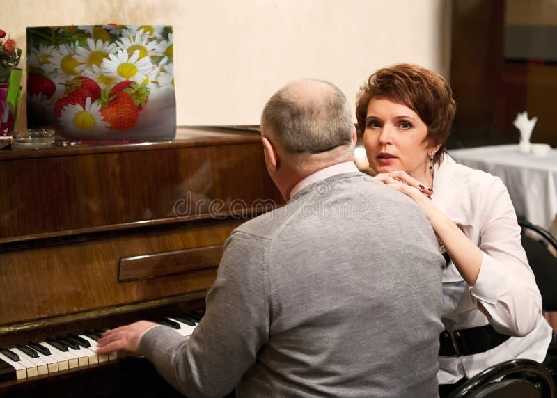 Bejaard paar in koffie bij piano royalty-vrije stock afbeelding