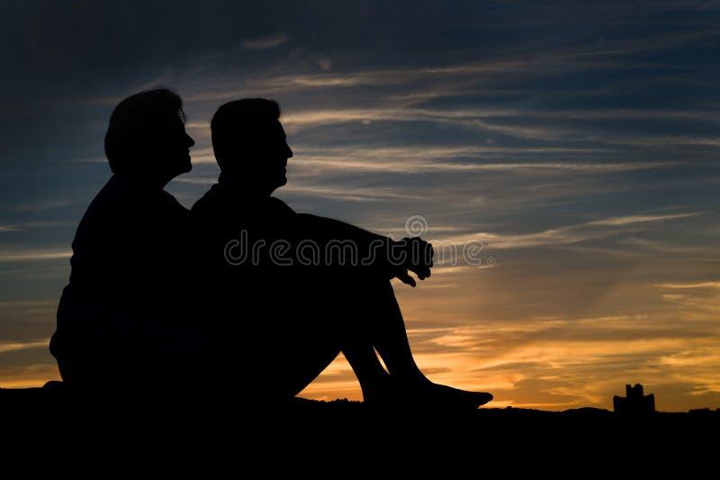 Bejaard paar in liefde bij zonsondergang stock afbeeldingen