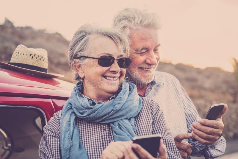 Bejaard paar met hoed, met glazen, met grijs en wit haar, met toevallig overhemd, op uitstekende rode auto op vakantie die van ti royalty-vrije stock foto