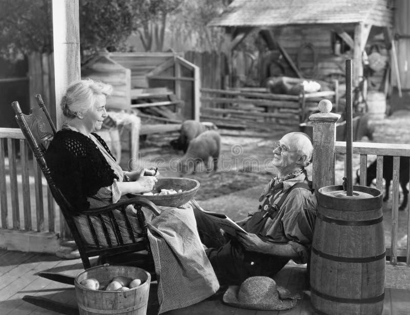 Bejaard paar op portiek van boerderij (Alle afgeschilderde personen leven niet langer en geen landgoed bestaat Leveranciersgarant royalty-vrije stock afbeelding