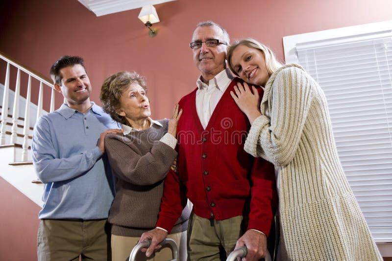 Bejaard paar thuis met volwassen kinderen royalty-vrije stock afbeelding