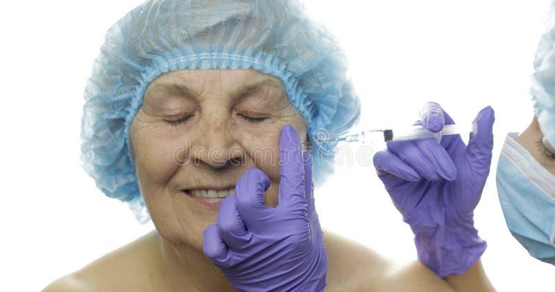Bejaard wijfje in beschermende hoed Arts die gezichtsinjecties voor pati?nt maakt stock foto