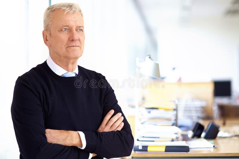 Bejaard zakenmanportret terwijl status met hun die wapens in het bureau worden gekruist royalty-vrije stock foto