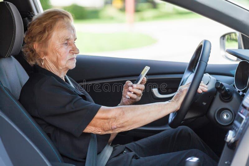 Bejaarde achter het stuurwiel stock fotografie