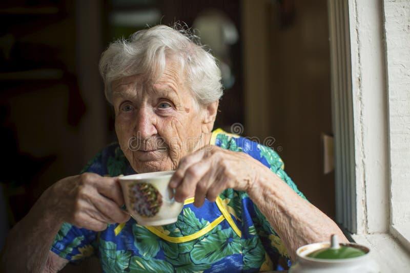 Bejaarde alleen het drinken thee gelukkig stock foto's
