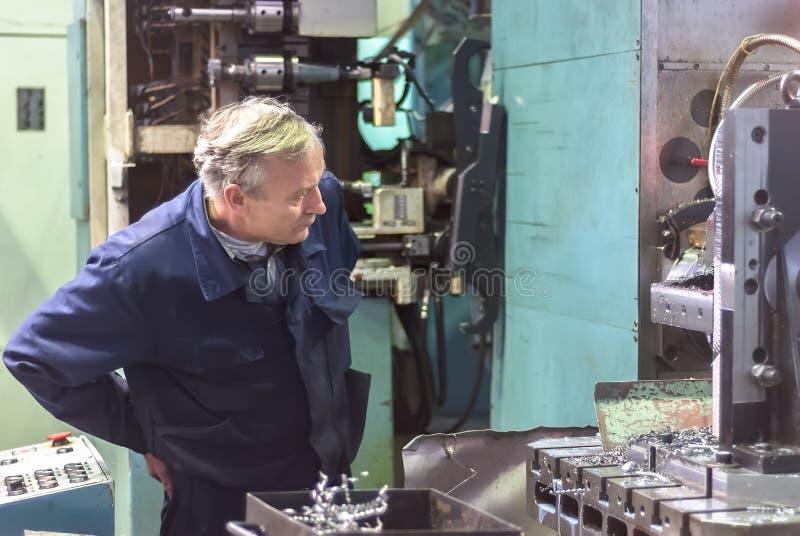Bejaarde arbeidershorloges op het werk van de malenmachine stock afbeeldingen