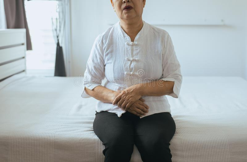 Bejaarde Aziatische vrouw die pijnlijke maagpijn op slaapkamer, Wijfje hebben die aan buikpijn lijden terwijl het liggen bij huis royalty-vrije stock foto's