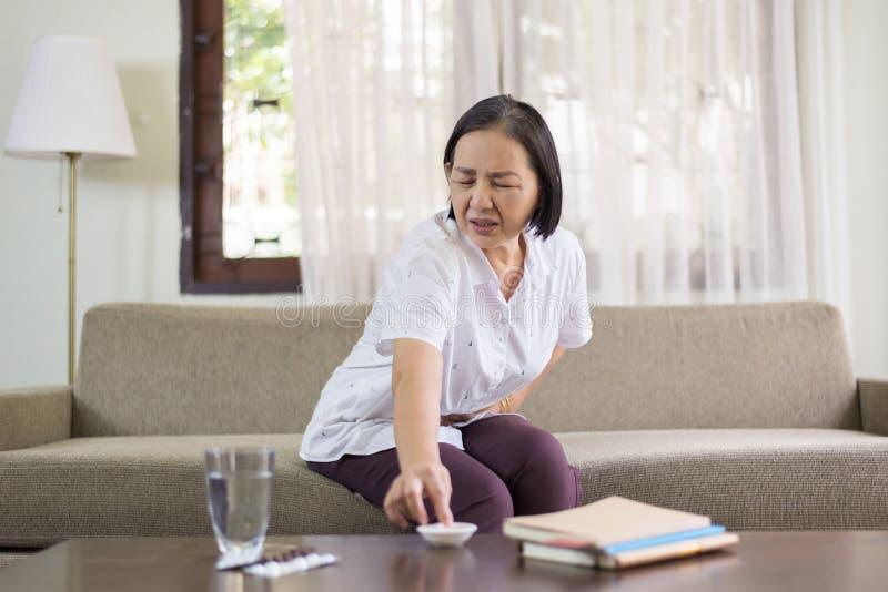 Bejaarde Aziatische vrouwen die pijnlijk hebben thuis, Hoger wijfje die aan buikpijn lijden stock foto's