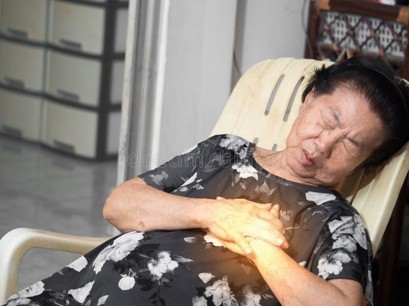 Bejaarde Aziatische vrouwenzitting op een stoel bij woonkamer met hartaanvallen Beide vrouwen` s handen op borst wegens hard adem royalty-vrije stock afbeelding