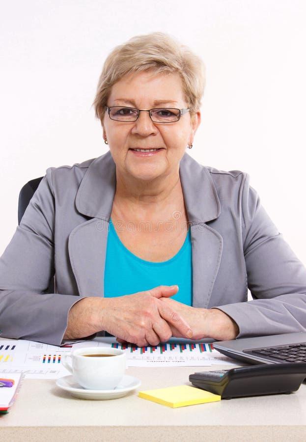 Bejaarde bedrijfsvrouw die bij haar bureau in bureau, bedrijfsconcept werken royalty-vrije stock foto's