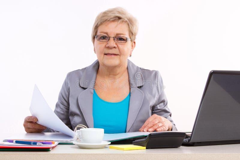 Bejaarde bedrijfsvrouw die met documenten bij bureau in bureau, bedrijfsconcept werken royalty-vrije stock afbeeldingen