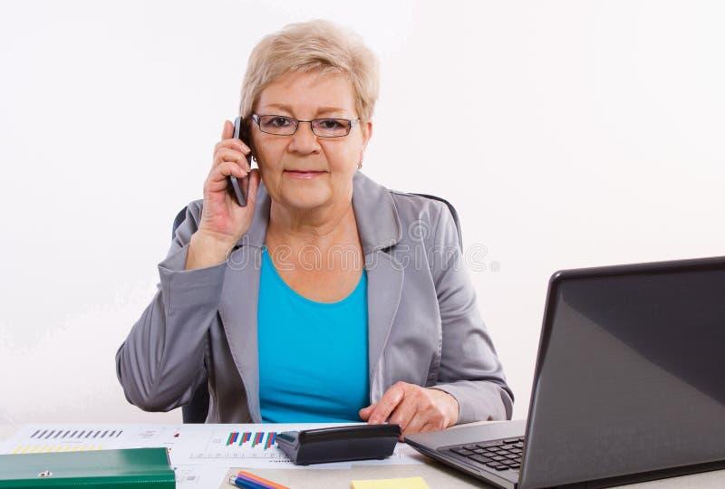 Bejaarde bedrijfsvrouw die op mobiele telefoon spreken en bij haar bureau in bureau, bedrijfsconcept werken stock afbeelding
