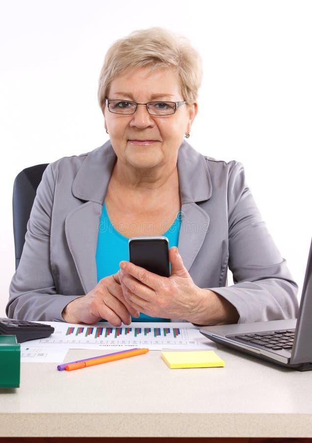 Bejaarde bedrijfsvrouw gebruikend mobiele telefoon en werkend bij haar bureau in bureau, bedrijfsconcept stock afbeelding