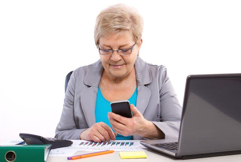 Bejaarde bedrijfsvrouw gebruikend mobiele telefoon en werkend bij haar bureau in bureau, bedrijfsconcept stock foto