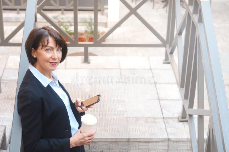 Bejaarde bedrijfsvrouw met koffie, die celtelefoon met behulp van, openlucht stock afbeeldingen