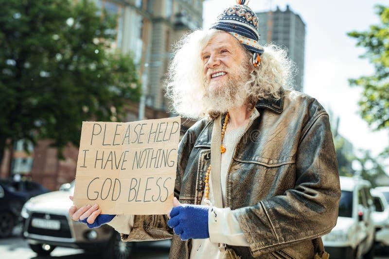 Bejaarde daklozen die oude kleren dragen die aan flarden voor hulp bedelen stock afbeelding