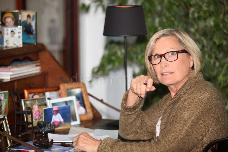 Bejaarde dame die bij bureau schrijft stock afbeelding