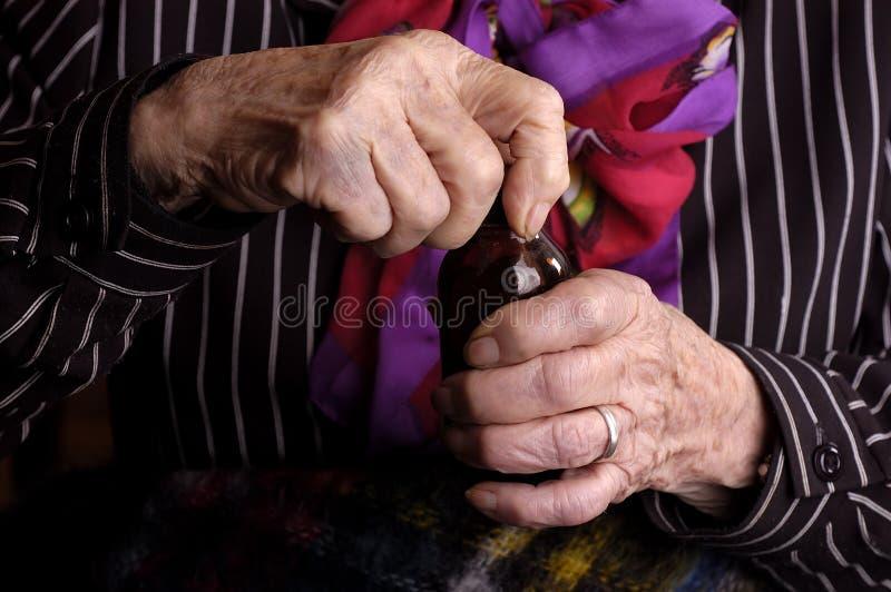 Bejaarde dame die een geneeskundefles opent stock foto