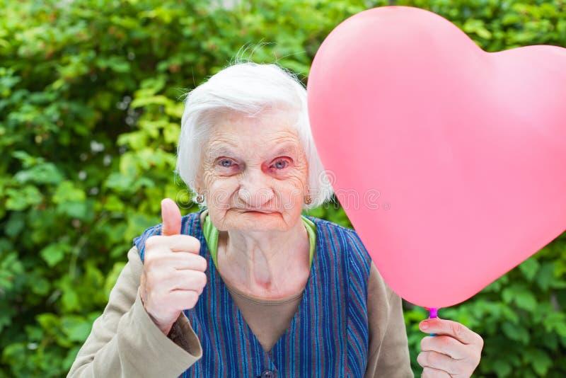 Bejaarde dame die een hart gevormde ballon houden royalty-vrije stock fotografie