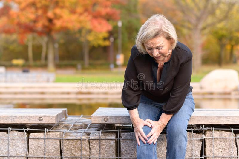 Bejaarde dame die haar knie in pijn grijpen royalty-vrije stock afbeeldingen
