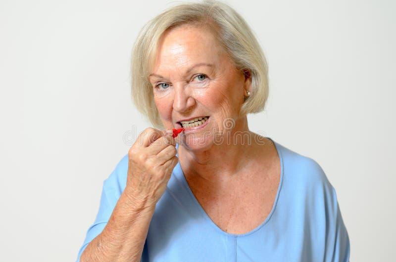Bejaarde dame die interdental borstel gebruiken stock fotografie