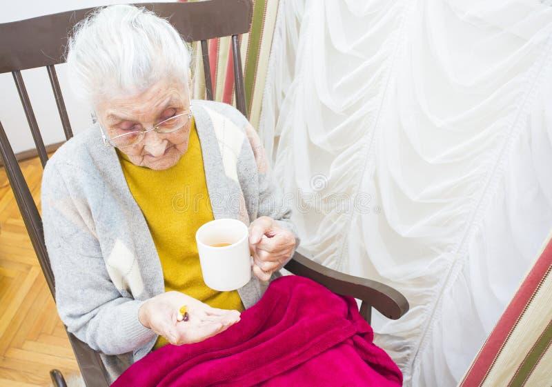 Bejaarde dame die medicijn nemen royalty-vrije stock afbeeldingen