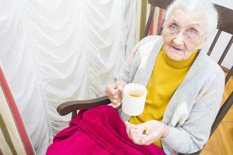 Bejaarde dame die medicijn nemen stock afbeeldingen