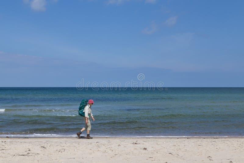 Bejaarde dame die op strand in Denemarken wandelen royalty-vrije stock foto