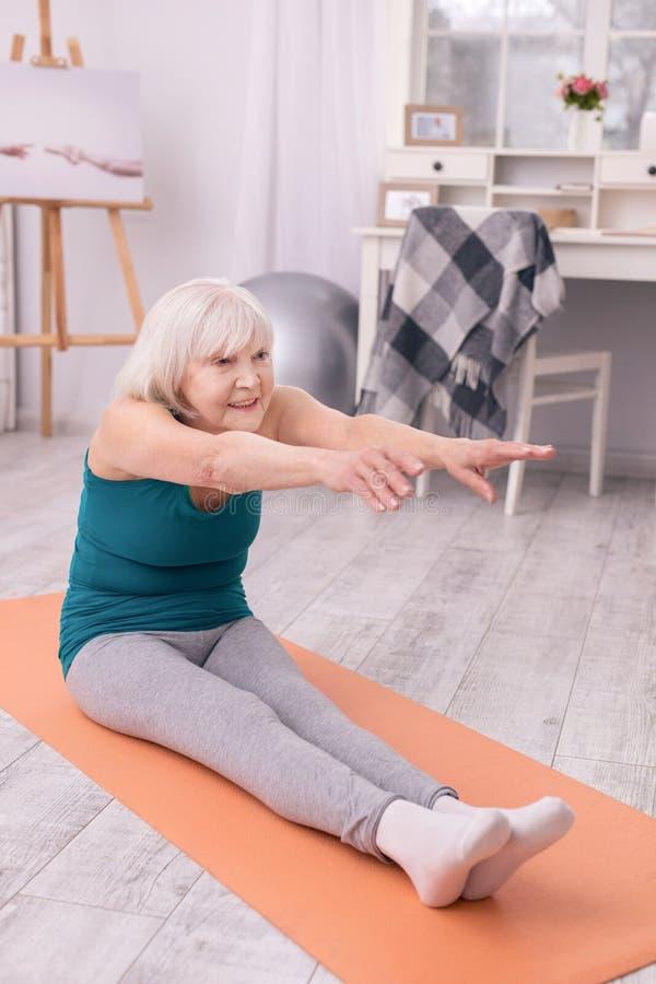 Bejaarde dame die terwijl het opwarmen vóór training uitrekken zich stock foto