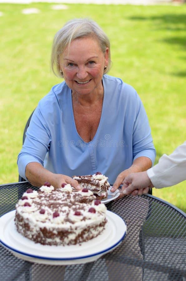 Bejaarde dame die van een plak van cake geniet royalty-vrije stock afbeeldingen
