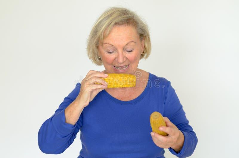 Bejaarde dame die van verse maïskolven genieten stock afbeeldingen