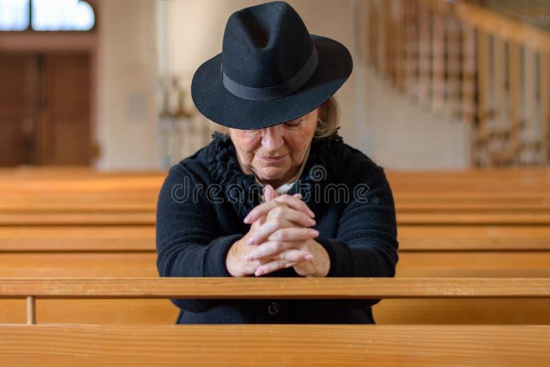 Bejaarde dame in het rouwen het bidden in een kerk royalty-vrije stock afbeelding